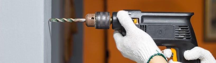 Para determinar qual é a furadeira correta, é necessário estipular a frequência de uso da máquina. Na imagem, uma pessoa está segurando a furadeira, perfurando uma parede.