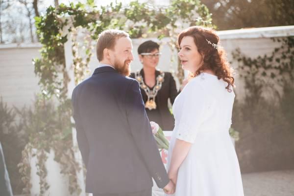 Formalności przy ślubie cywilnym: Fotografia ślubu cywilnego w plenerze, zawartego przed urzędnikiem państwowym. Zdjęcie wykonane w trakcie kameralnej uroczystości na styku Sopotu i Gdańska, kilkadziesiąt metrów od morza.