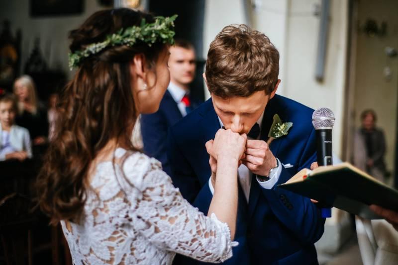 Przebieg ślubu kościelnego - Zdjęcie w trakcie ślubu w kosciele pod wezwaniem Św. Mikołaja w Gdańsku. Pan Młody całuje obrączkę, którą nałożył chwilę wcześniej na dłoń Pani Młodej. Pani Młoda całuje zazwyczaj obrączkę przed włożeniem jej na palec Pana Młodego.