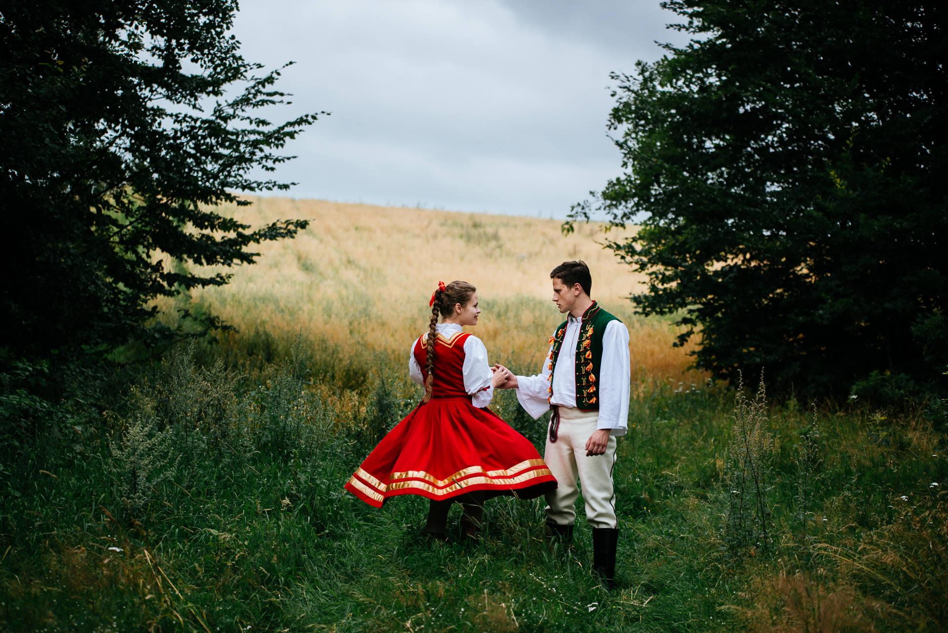 Rustykalna sesja ślubna, z użyciem strojów ludowych, zrealizowana w skansenie na Kaszubach, w otoczeniu lasów, łąk i pól. Fot. Rafał i Magda Nitychoruk