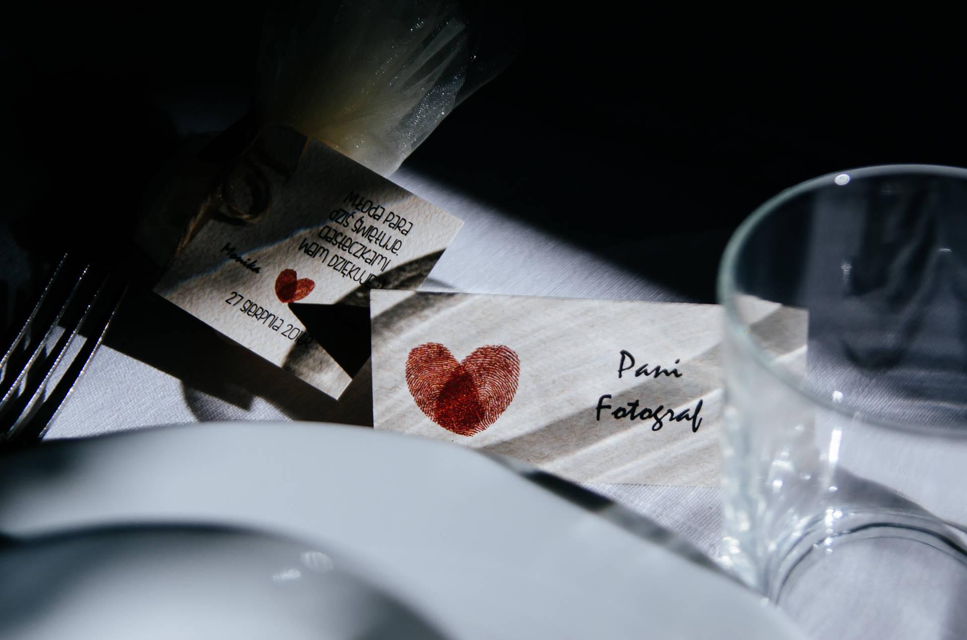 Na stołach naszykowano winietki - ta na zdjęciu uwzględnia obecność fotografów, którzy są poniękąd gośćmni na weselu