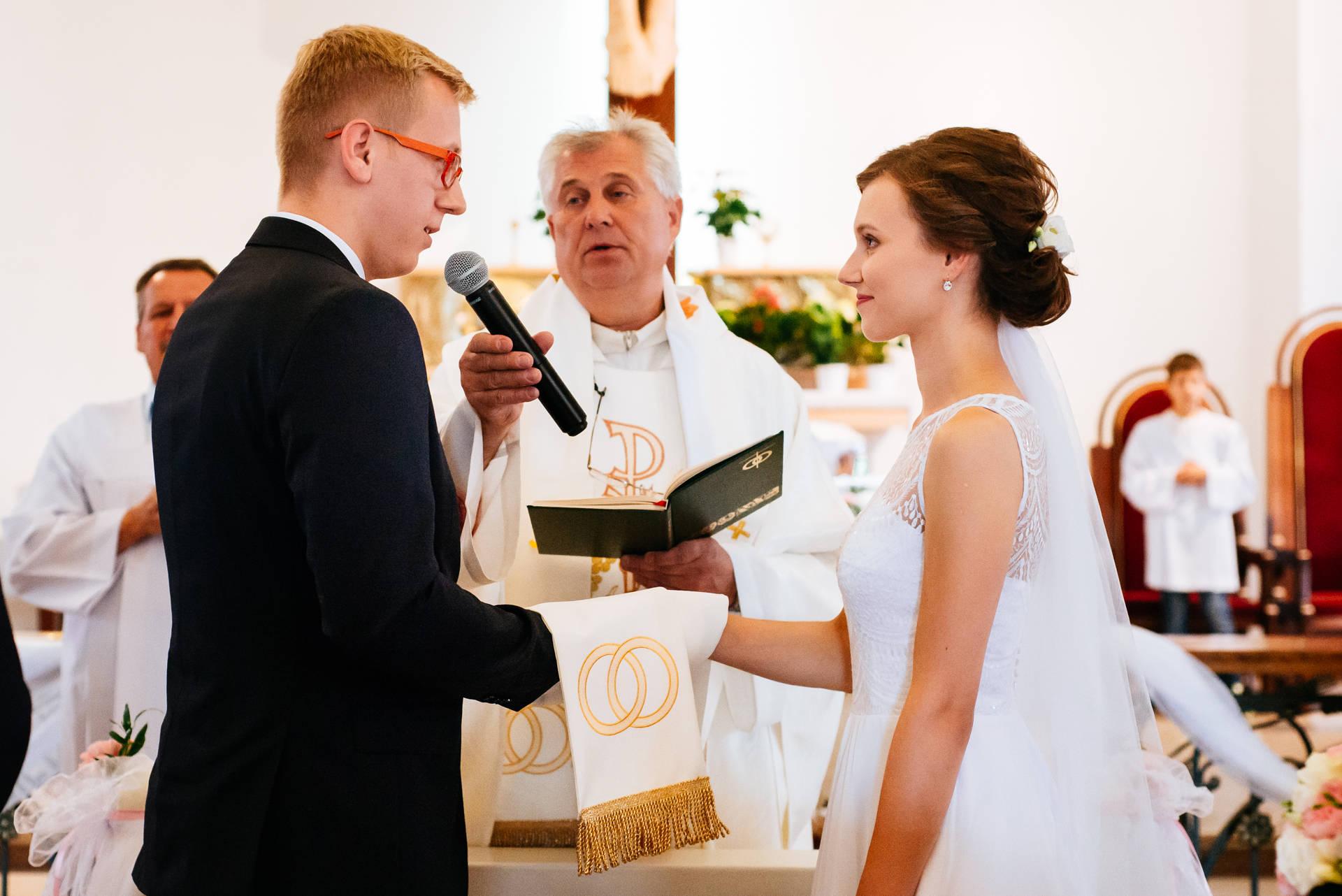 Zdjęcie wykonane w trakcie skłądania przysięgi ślubnej, w trakcie konkordatowego ślubu kościelnego. Dużym wyzwaniem dla nas jako fotografów ślubnych było uchwycenie sceny bez zarejestrowania kamerzystów.
