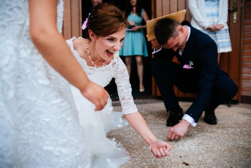 poradnik ślubny - niezbędnik gościa weselnego - zdjęcie przedstawia parę młodą zbierającą monety. Jest to nieodłączny element w przebiegu ślubu kościelnego, choć nie jest pochwalany przez Kościół Katolicki.
