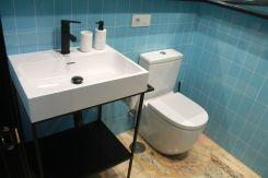 Lavabo e inodoro con alicatado vertical azul en Apartamento Lapamán