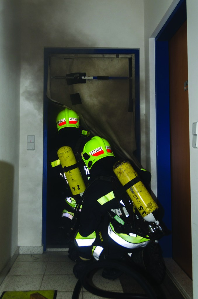 Firefighters using a smoke curtain device to isolate fire from stairwell. Picture courtesy of Dr. Michael Reick