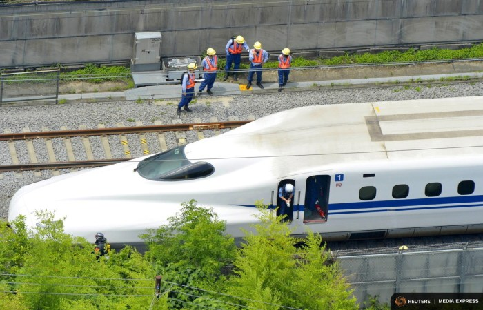 Police officers investigate a Shinkansen bullet train after it made an emergency stop in Odawara, south of Tokyo, in this aerial view photo taken by Kyodo June 30, 2015. REUTERS/Kyodo
