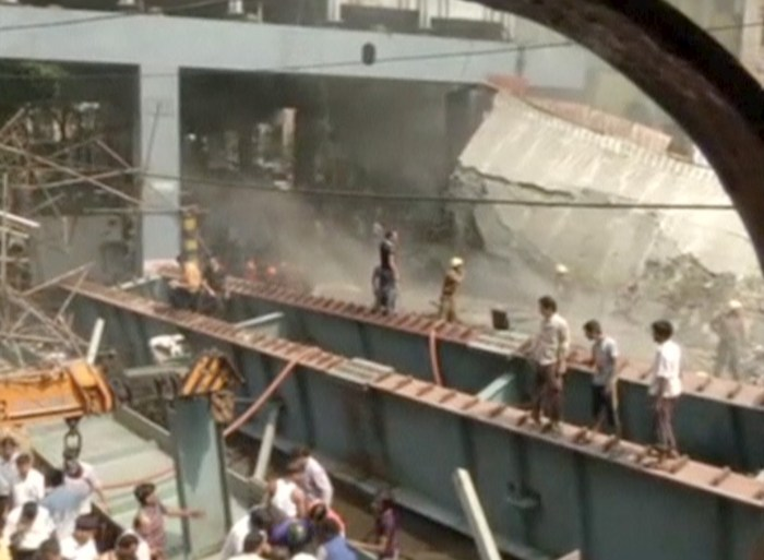 People are seen standing on the debris of a a flyover which collapsed, in Kolkata, India, in this still image taken from video March 31, 2016. REUTERS/ANI via Reuters TV