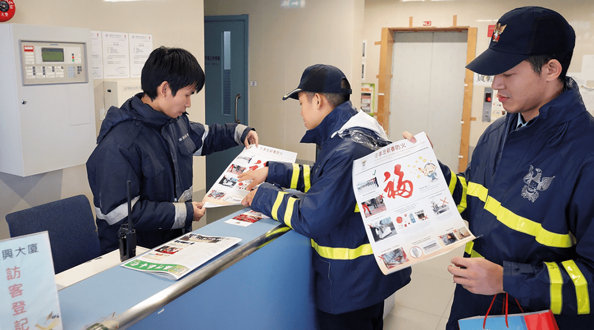 Fire Officers distribute the fire prevention posters to the caretakers.