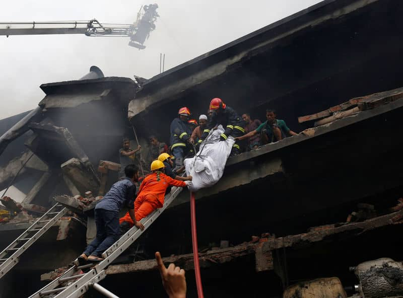 Firefighters remove a dead body at a food and cigarette packaging factory after fire broke out outside of Dhaka, Bangladesh, September 10, 2016. REUTERS/Mohammad Ponir Hossain