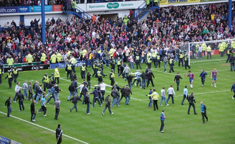 Crowd of soccer fans surge onto the field following the victory of a critical match.