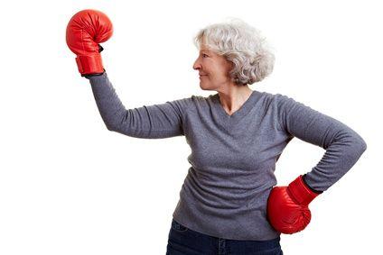 Glückliche Seniorin boxt mit roten Boxhandschuhen