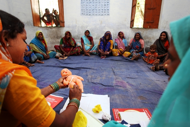 Expecting mothers and their mother-in-laws learn about how to safely sever the umbilical cord of a newborn at a Sure Start facilitated Mothers' Group Meeting in Sabji Village, Rae Bareilly District, Uttar Pradesh, India