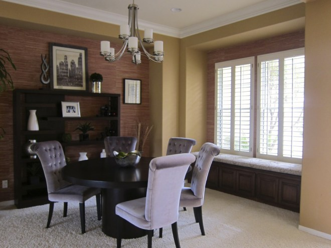 A custom window seat cushion unifies the space by coordinating with the grey velvet dining chairs.