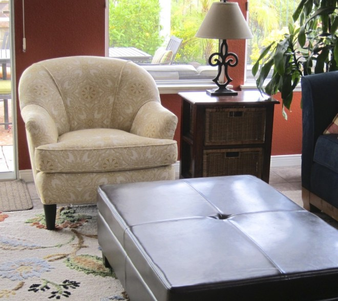 An oversized chair was replaced with this vintage find which was reupholstered in a more contemporary style and fabric.  A leather storage ottoman was also added.