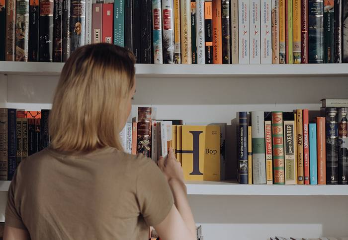 women looking at books on shelf