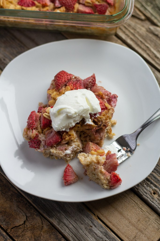 Slice of strawberry baked oatmeal with a bite on a fork