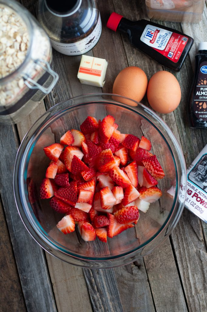 Ingredients for healthy strawberry baked oatmeal: eggs, oats, maple syrup, butter, vanilla extract, baking powder and fresh strawberries