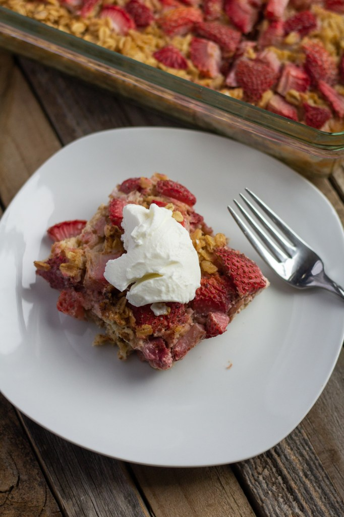 Slice of healthy strawberry baked oatmeal with Greek yogurt on top