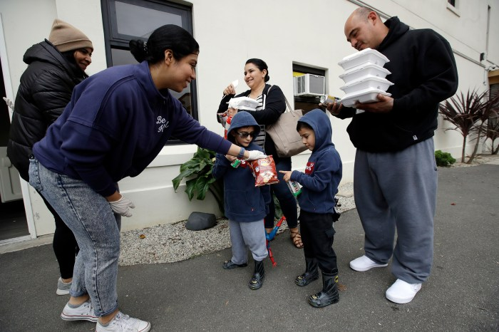 Volunteer Pahola Campos, second from left, hands out lunches to the Garcia family — mom Marie, dad Sergio, at right, and their children — on Mar. 16 at a food distribution center set up by the Dream Center for those in need due to the coronavirus outbreak in Los Angeles