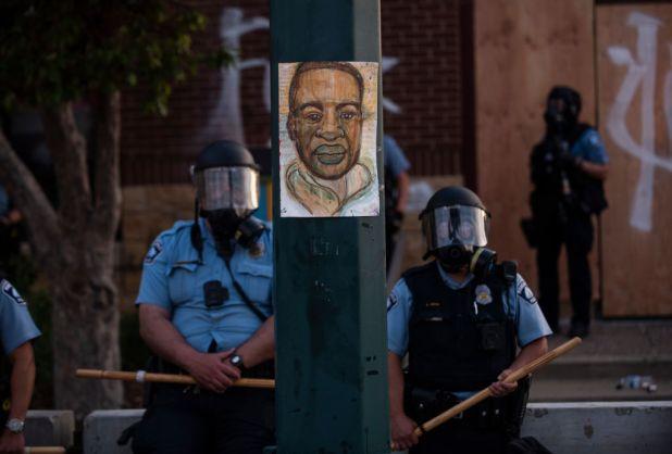 Un retrato de George Floyd cuelga de un poste de luz de la calle mientras los oficiales de policía hacen guardia en el Tercer Recinto Policial durante un enfrentamiento con un grupo de manifestantes en Minn., Minnesota, 27 de mayo de 2020.