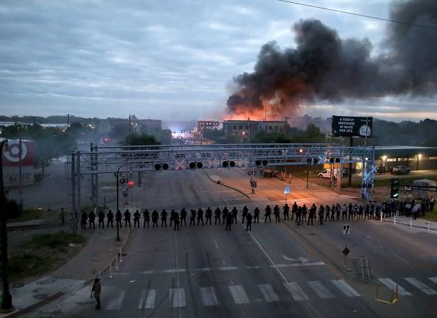 Los agentes de la ley se congregaron a lo largo de Lake Street, cerca de la avenida Hiawatha, mientras los incendios ardían después de una noche de disturbios y protestas por la muerte de George Floyd en Minneapolis, Minnesota, el 29 de mayo.