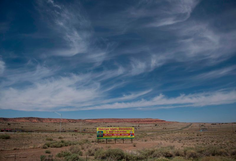 A sign promoting social distancing sits near the Navajo Nation town of Chinle during the 57 hour curfew imposed to try to stop the spread of the Covid-19 virus through the Navajo Nation, in Arizona on May 23, 2020.