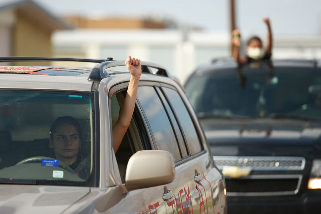 Protesters participate in a car caravan to increase the pressure on ICE to release GEO detainees in front of GEO Aurora ICE Processing Center in Aurora, Colorado. April 9, 2020.