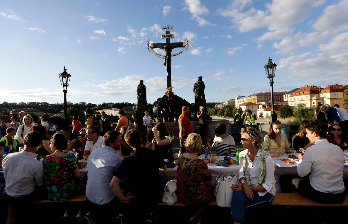 Residents sit to dine on a 500 meter long table set on the medieval Charles Bridge, after restrictions were eased following the coronavirus pandemic in Prague, Czech Republic, Tuesday, June 30, 2020.