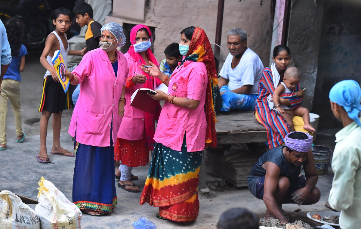 New Delhi, June 25: ASHAs talk amongst themselves while conducting door to door survey to identify COVID-19 cases. Photo by Raj K Raj/Hindustan Times via Getty Images