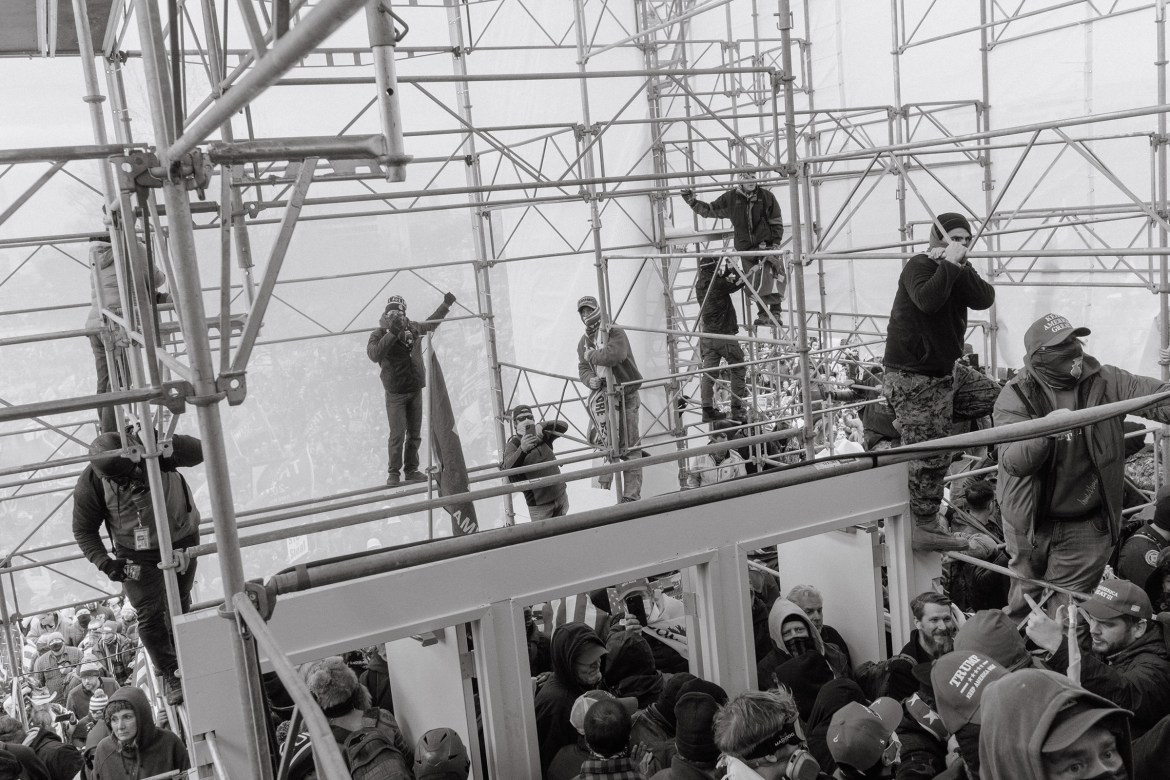 Pro-Trump rioters climb the scaffolding outside of the Capitol.