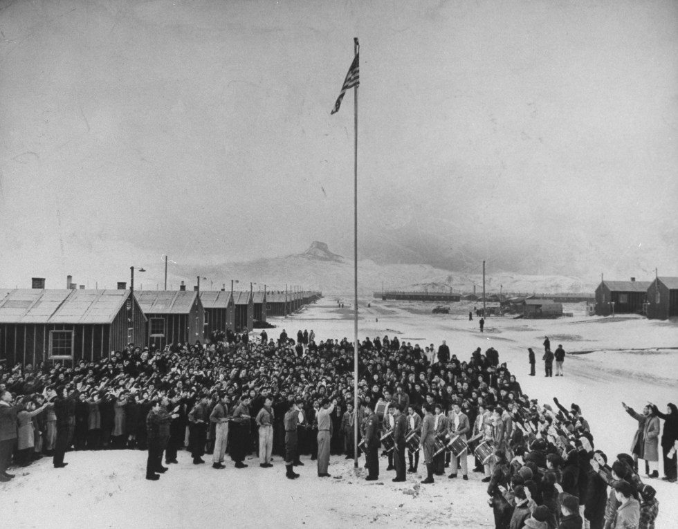Nisei Japanese-Americans participating in a flag saluting ceremony at relocation center in forced internment during WWII, 1942