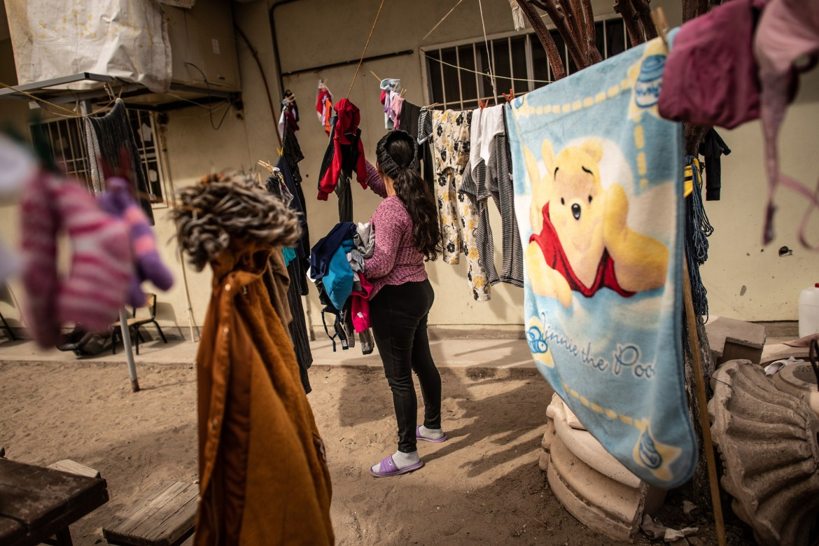 Carmen, a migrant fleeing violence in El Salvador, hangs her laundry to dry on a clothesline.