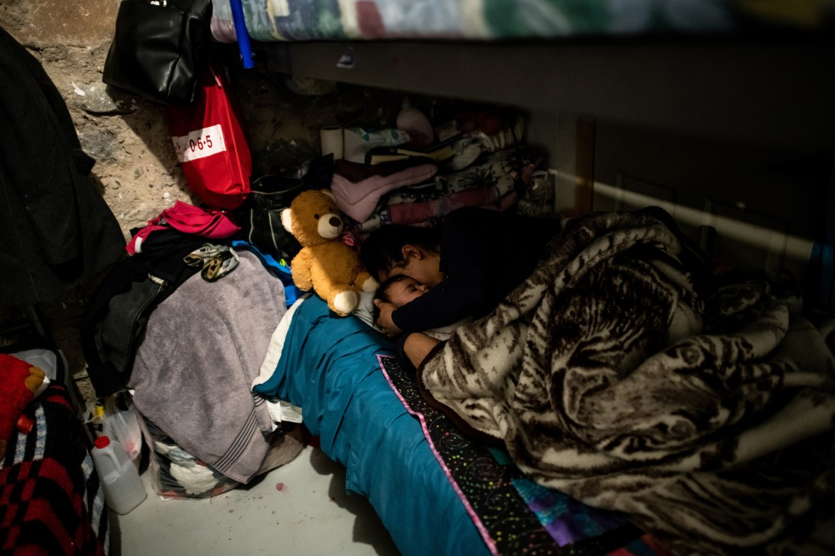 Xiomara lays down with her baby in one of the dormitories.
