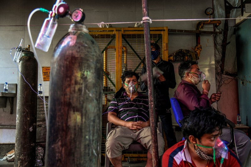 With hospitals full, COVID-19 patients receive oxygen outside a Sikh temple in Delhi on April 25.