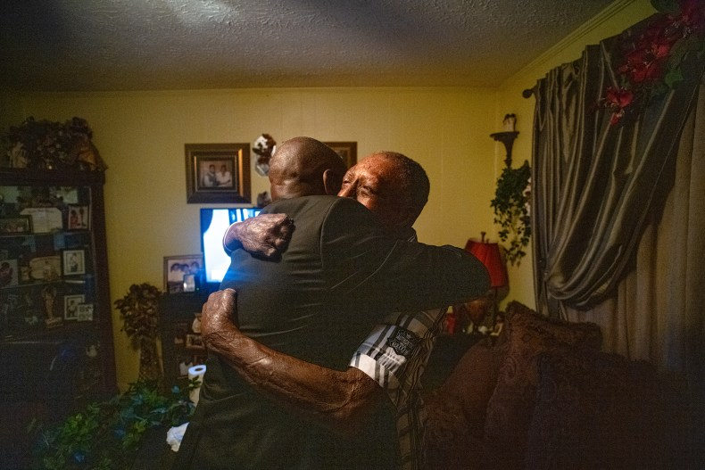 Crump hugs Curtis Jones, a client who was severely burned after an explosion at a manufacturing facility supplying the Department of Defense, at home in Tallahassee, Fla., on April 3.