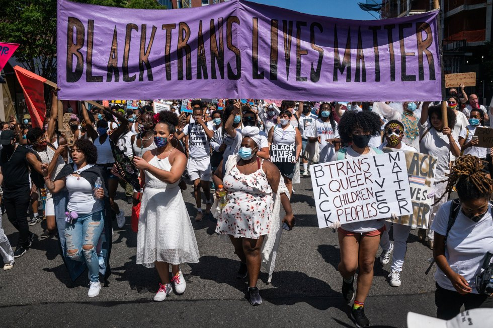 "Demonstrators carry a banner reading ""Black Trans Lives Matter"" during a march in New York, on June 14, 2020."
