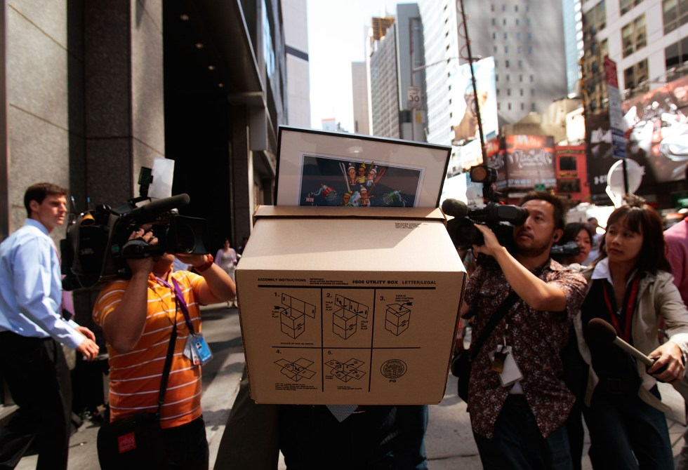 An employee of Lehman Brothers Holdings Inc. carries a box out of the company's headquarters as he is followed by the media Sept. 15, 2008 in New York City.