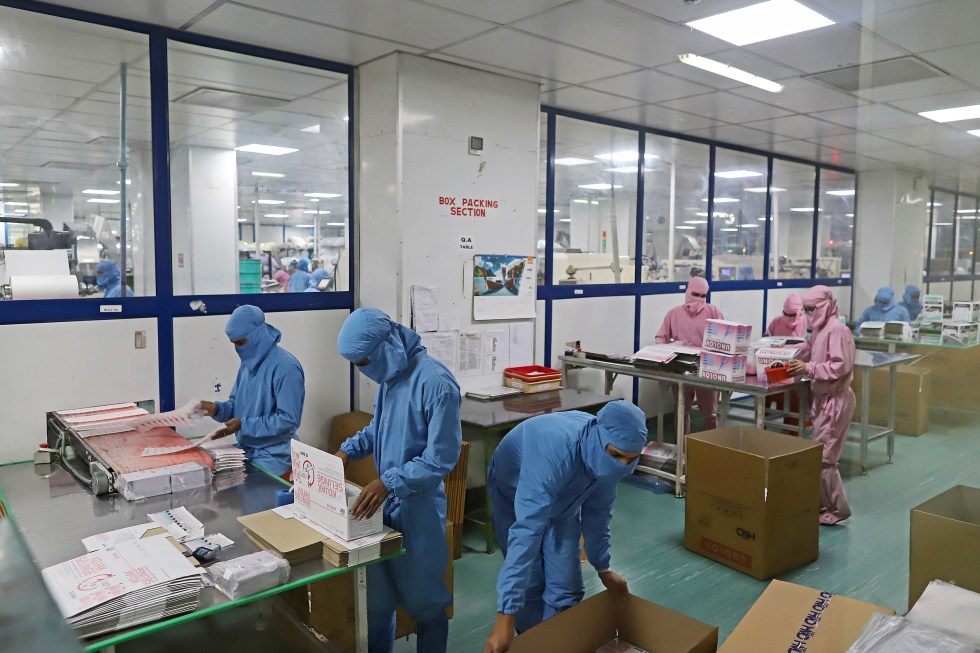 Employees pack boxes of syringes on the production line at the Hindustan Syringes and Medical Devices Ltd. facility in Faridabad, Haryana, India, on March 11, 2021.