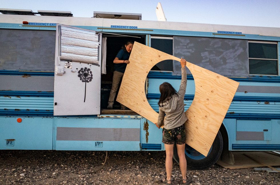 """Paula and Max carry in a piece of wood to mount around Max's """"hobbit bed"""" on the school bus, outside Ehrenberg, Az., on Feb. 8."""