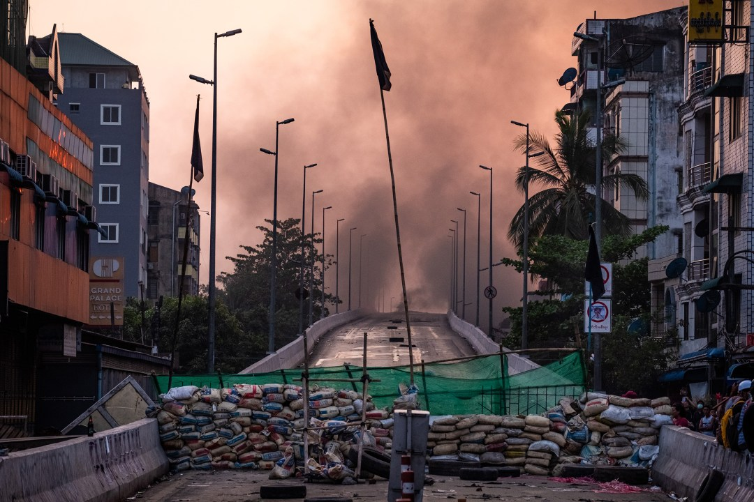 Smoke rises from tires burning near a barricade erected by protesters to stop government forces from crossing a bridge in Yangon on March 16, 2021.