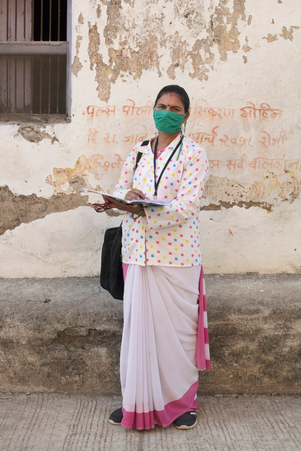 Portrait of Archana Ghugare, a community health worker, in Pavnar, Maharashtra, India, on Dec. 1, 2020. In the background is a message encouraging people to bring their children for the Polio vaccine drive.