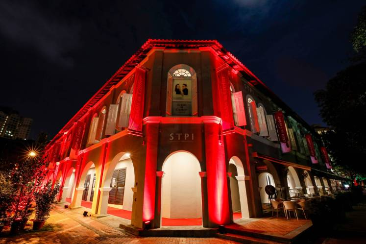 The outer facade of the Clash de Cartier Studio in Singapore all lit up in red.