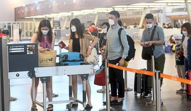 预防措施:乘客在雪邦KLIA 2的出发航站楼扫描行李时戴着口罩。
