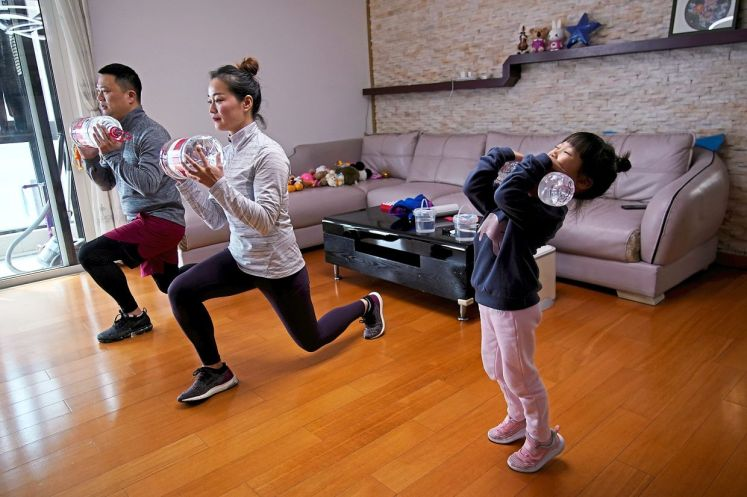 A family in Shanghai. China, exercises as they watch an online fitness class while confining themselves to their homes during the Covid-19 outbreak. Dr Sanjiv did the same during his self-isolation period as he could not go to the gym to work out. — Reuters