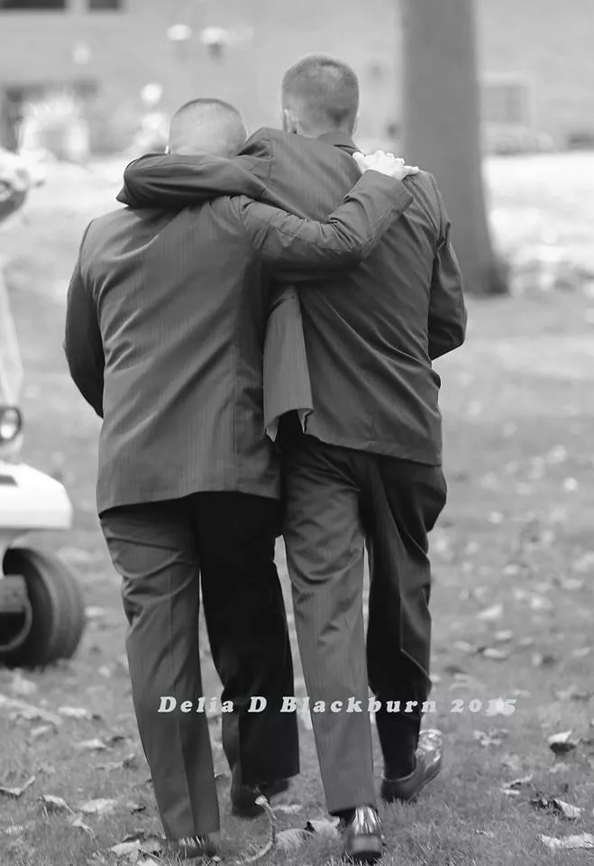 Dad and stepdad hugging