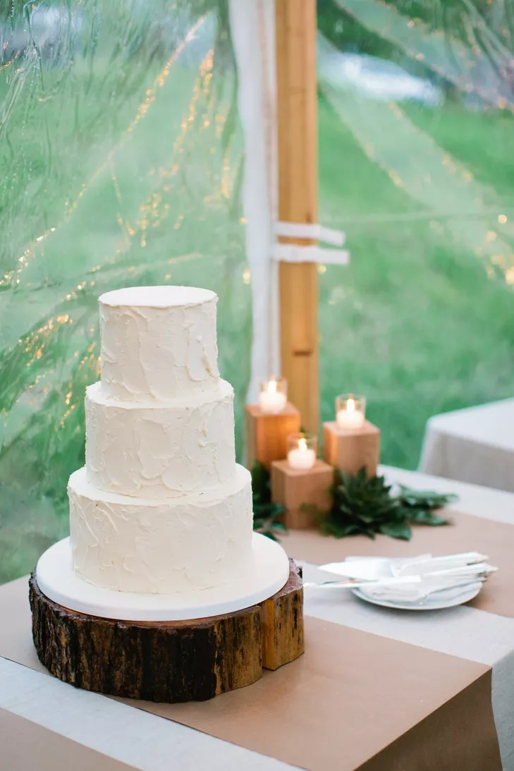 White Buttercream Wedding Cake On Wood Stand