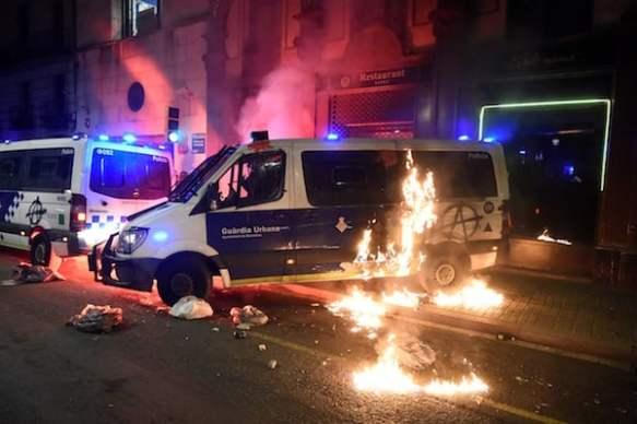 Police van torched in Barcelona protest against rapper's jailing
