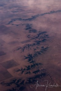 Aerial view of the arid western landscape, eroded cliffs and canyons cut through patchwork agricultural land