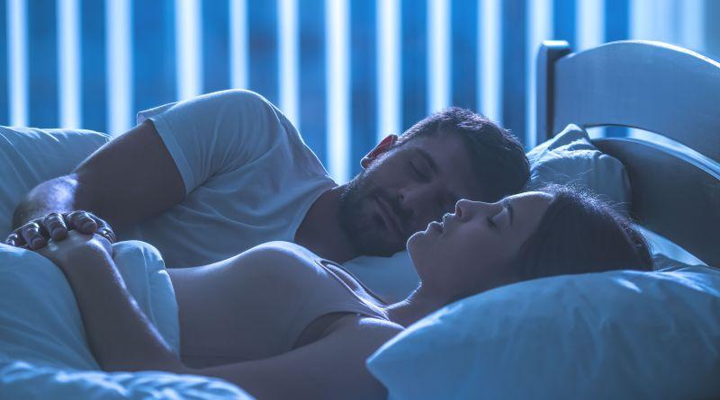 Pärchen liegt im Bett und schläft gut. Schlafprobleme