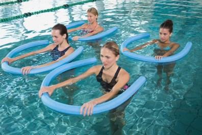 Personen machen im Wasser Aquagymnastik. rheumatische Beschwerden